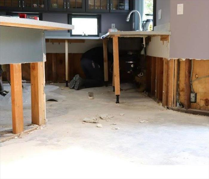 Wood flooring in kitchen is wet and dehumidifier is placed on floor.
