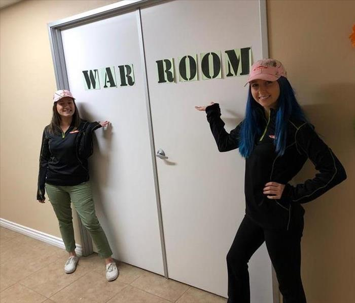 "two females pointing to doors that say ""war room"""