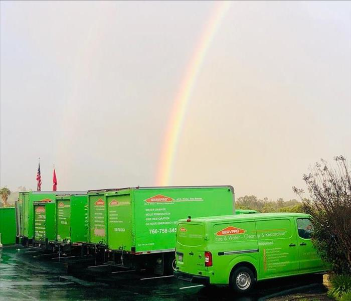 Rainbow pointing to SERVPRO green trucks.